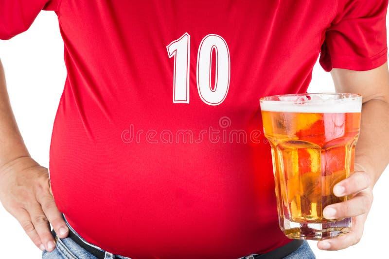 Beleibter Mann mit dem dicken Bauch, der ein Glas Auffrischung des kalten Bieres hält stockbild