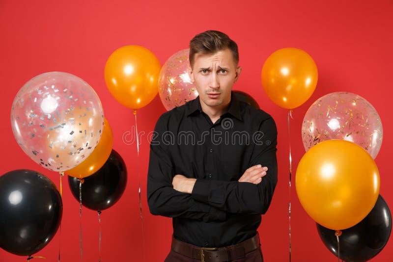 Beleidigter junger Mann im schwarzen klassischen Hemdhändchenhalten gefaltet auf hellen roten Hintergrundluftballonen St.-Valenti lizenzfreie stockfotografie