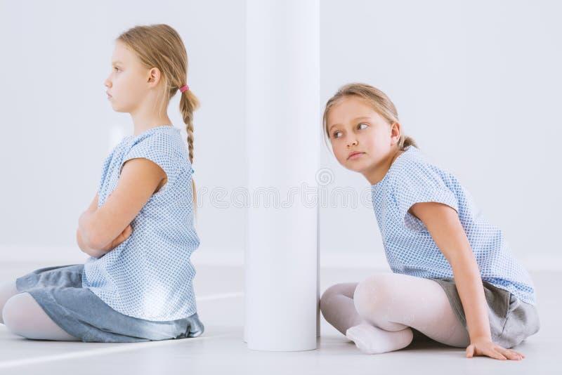 Beleidigtes Mädchen und Zwillingsschwester stockfoto