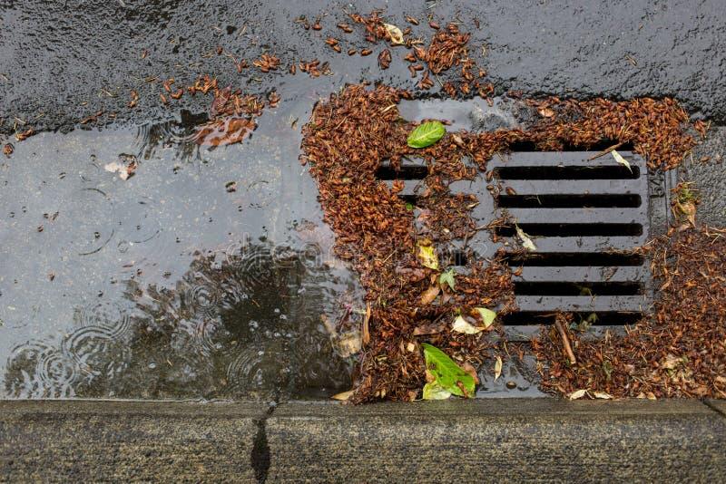 Belemmerde een straatafvoerkanaal tijdens een regenonweer stock foto's