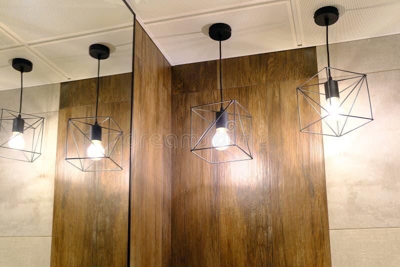 Beleuchten der Toilette Hängende Lampen werden im Spiegel reflektiert lizenzfreies stockfoto
