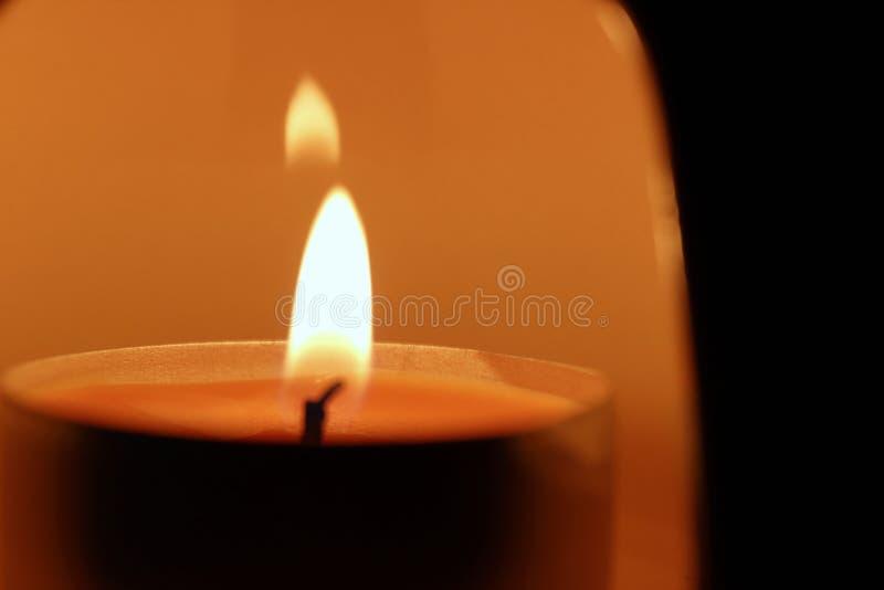 Beleuchten Sie eine Kerze in der Dunkelheit stockfotos