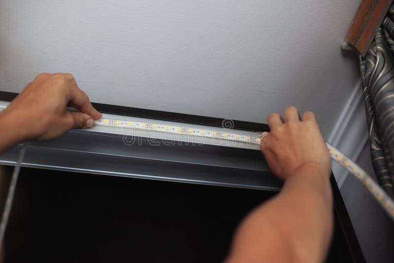 Beleuchtend installieren Sie, der Meister macht die Installation von LED-Streifen auf den oberen Nischen des Kabinetts zu Hause stockbilder