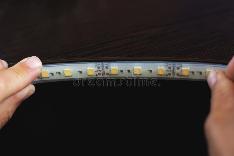 Beleuchtend installieren Sie, der Meister macht die Installation von LED-Streifen auf den oberen Nischen des Kabinetts zu Hause lizenzfreies stockfoto