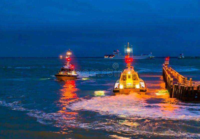 Beleuchtete Boote, die nachts im Hafen von Vlissingen, die Pieranlegestelle am Abend, Zeeland, die Niederlande segeln lizenzfreie stockfotografie