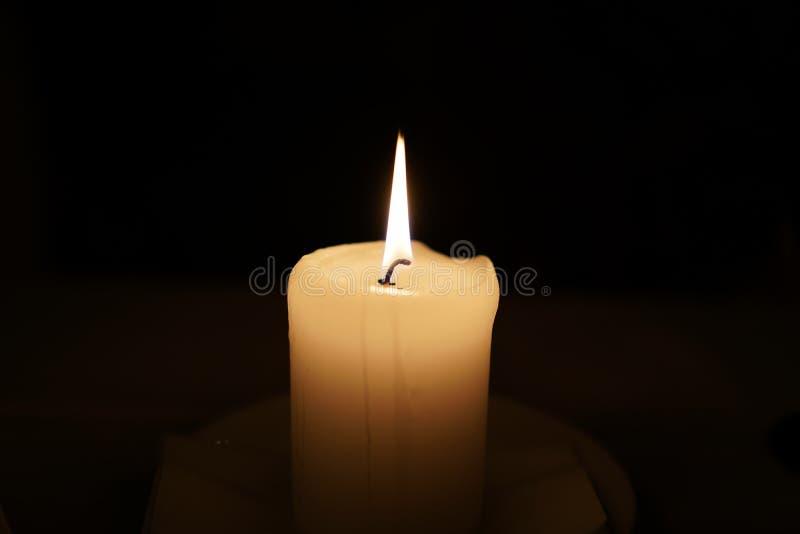 Beleuchtete einzelne Kerze Selektiver Fokus der Kerze Leuchten Sie Feuer durch Kerze auf einem dunklen Hintergrund lizenzfreie stockfotos