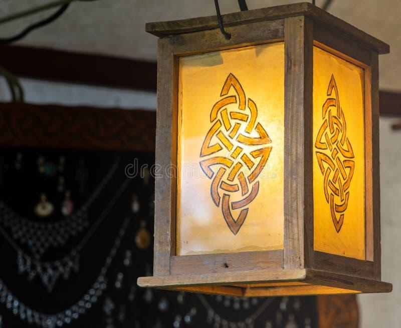 Beleuchtete Laterne mit einem abstrakten Muster, das einer Rune, Holzrahmen mit gelbem Glas ähnelt stockfotos