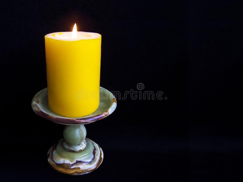 Beleuchtungskerzenhalter Onyx mit gelber Kerze auf einem schwarzen Hintergrund stockbilder