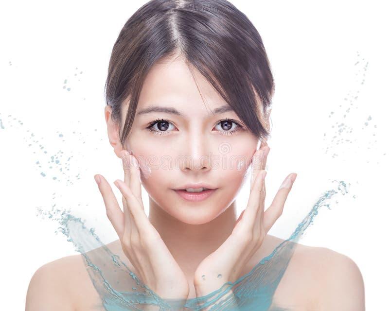Beleza asiática que aplica o creme à cara com respingo da água fotografia de stock