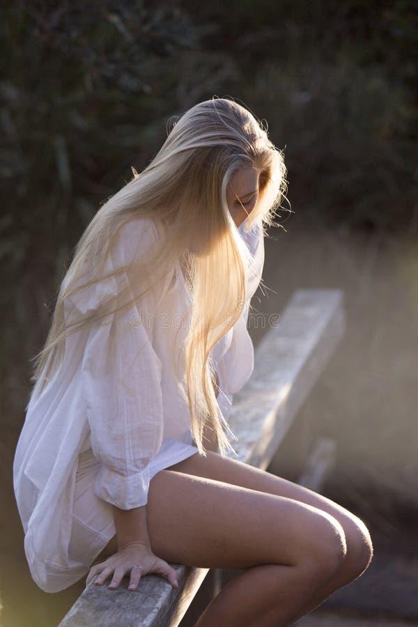 A beleza australiana com cabelo louro longo olha para baixo com o Sun que flui através do cabelo foto de stock royalty free