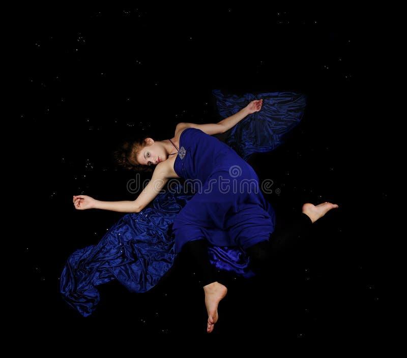 Beleza caucasiano no vestido azul que flutua no preto foto de stock royalty free