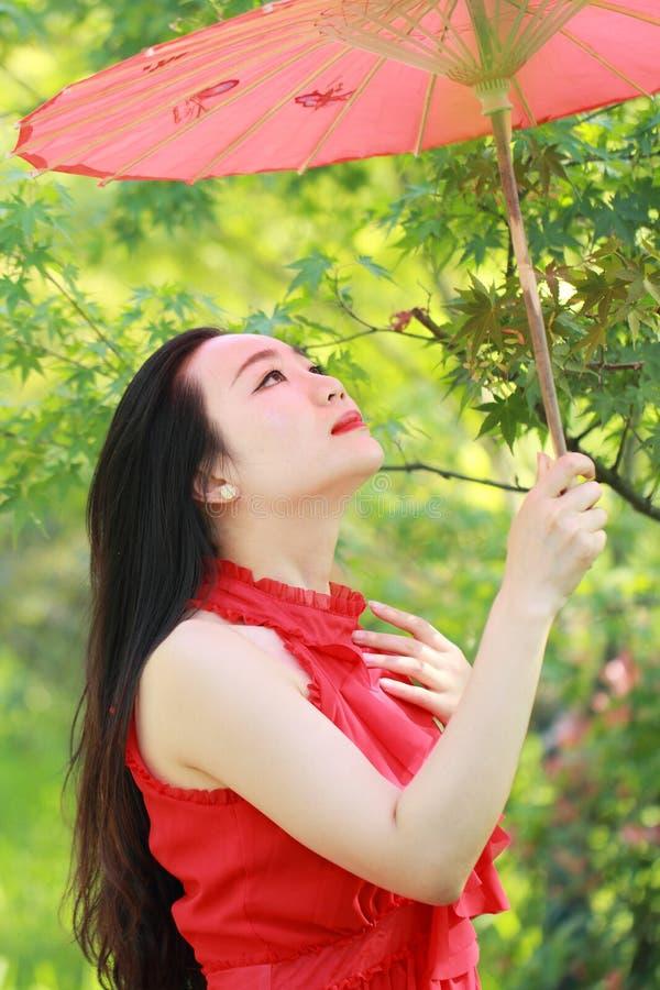 Beleza chinesa asiática na excursão vermelha do vestido em um parque imagens de stock royalty free