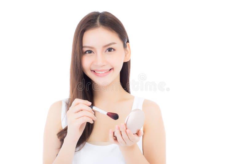 A beleza da aplicação asiática da mulher do retrato compõe com a escova do mordente isolada no fundo branco fotos de stock
