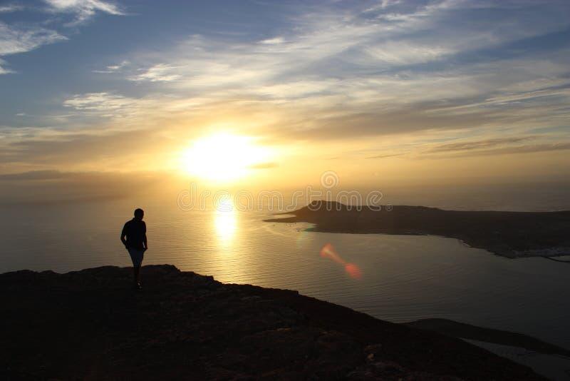 A beleza de uma opinião do por do sol relógio pelo homens de uma distância Sob o céu alaranjado azul fotos de stock