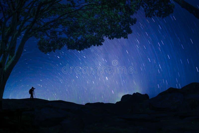 A beleza do céu na noite com das estrelas as árvores igualmente nas montanhas e em um fotógrafo que capture o momento fotos de stock royalty free