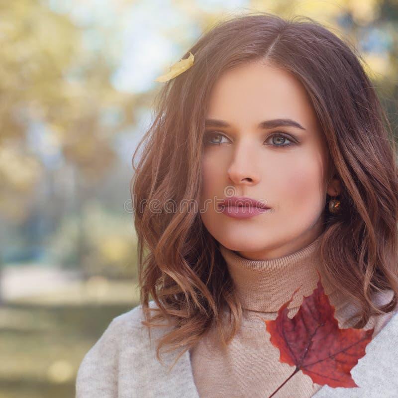 Beleza do outono Jovem mulher com as folhas da queda no cabelo ondulado fotografia de stock royalty free