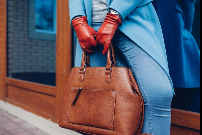 Beleza e fôrma Revestimento vestindo à moda e luvas da mulher elegante, guardando a bolsa marrom do saco imagens de stock