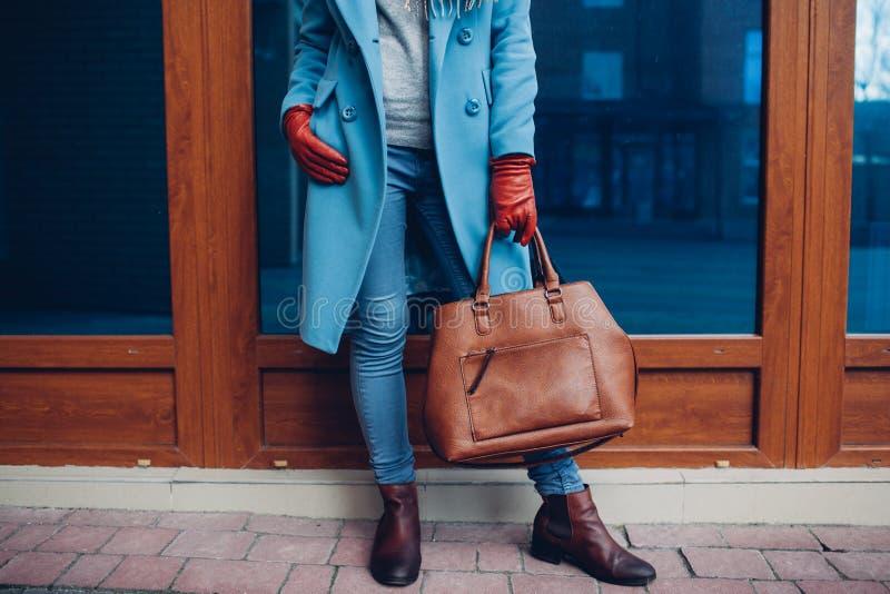 Beleza e fôrma Revestimento vestindo à moda e luvas da mulher elegante, guardando a bolsa marrom do saco fotos de stock