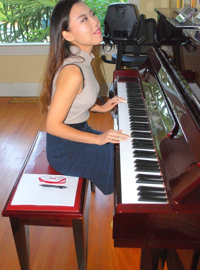 Beleza fêmea asiática que joga o piano imagem de stock