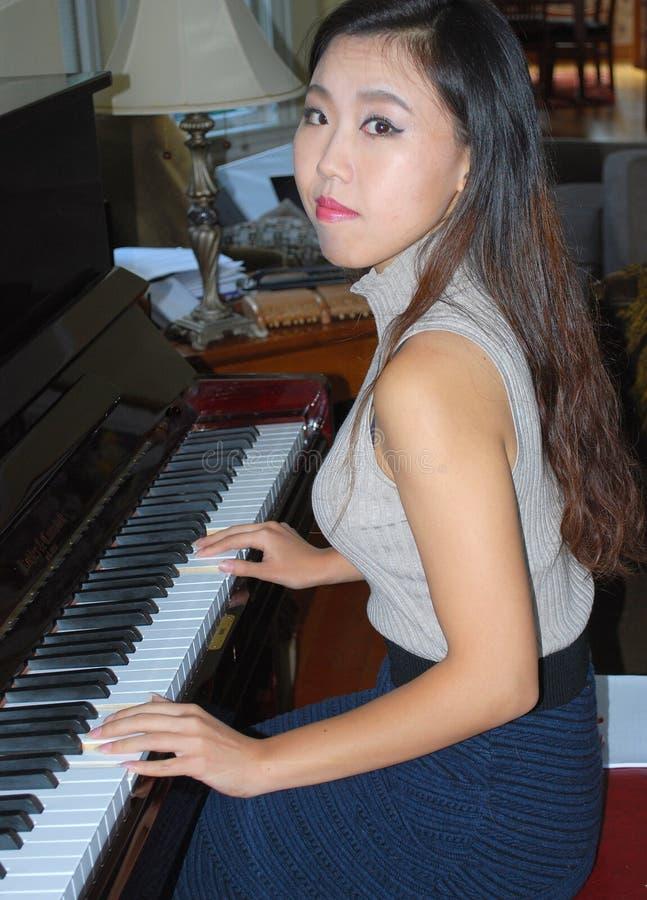 Beleza fêmea asiática que joga o piano fotografia de stock