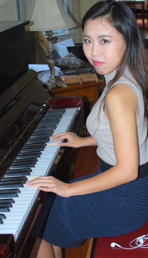 Beleza fêmea asiática que joga o piano foto de stock royalty free