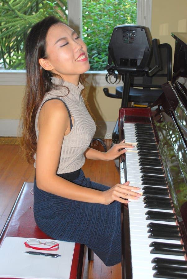 Beleza fêmea asiática que joga o piano fotos de stock
