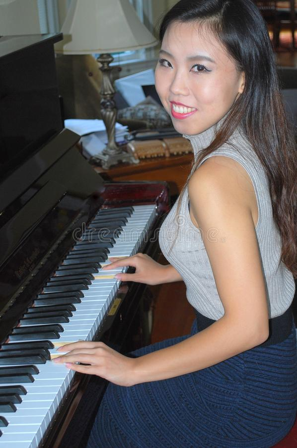 Beleza fêmea asiática que joga o piano foto de stock
