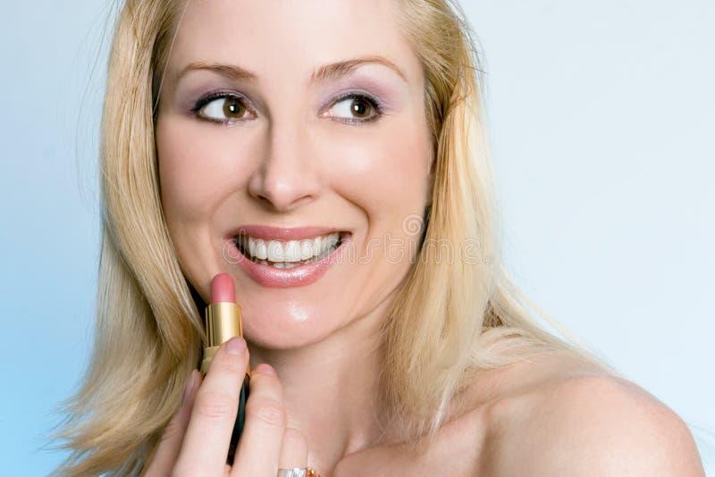 Beleza - fêmea feliz que aplica o batom cor-de-rosa fotografia de stock royalty free