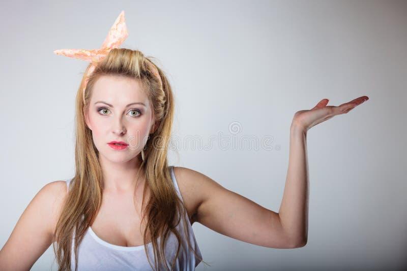 Beleza, forma, conceito da propaganda - pino retro da jovem mulher acima da palma aberta da terra arrendada do hairband do estilo imagem de stock
