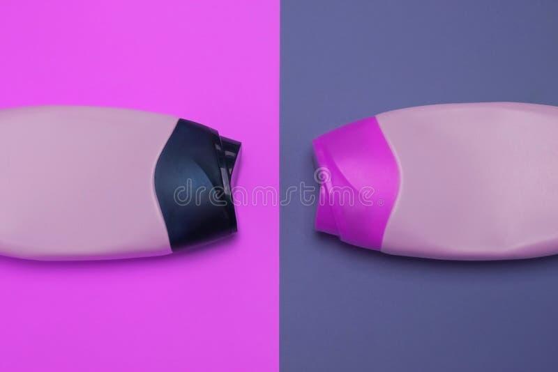 Beleza, garrafas decorativas dos cosm?ticos Rosa e fundo roxo das cores, configura??o lisa, vista superior, estilo minimalistic d fotos de stock