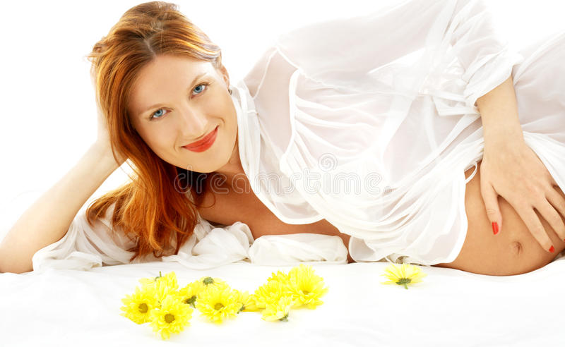 Beleza grávida de sorriso com flores imagem de stock