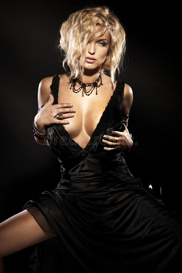 Beleza loura 'sexy' que senta-se no vestido preto elegante imagem de stock