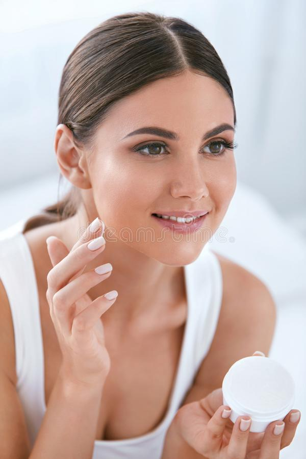 beleza Mulher bonita que aplica o creme de cara na pele facial macia foto de stock