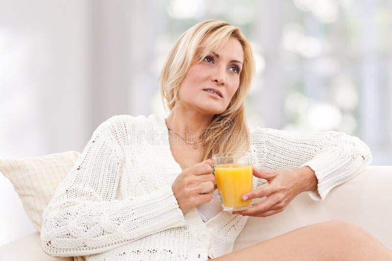 Beleza, mulher do blondie com um vidro do sumo de laranja fotos de stock
