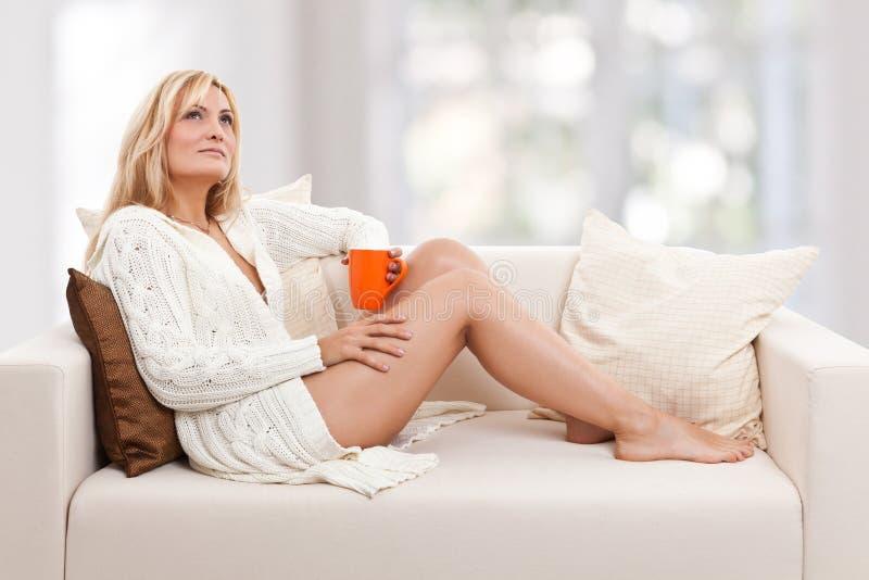 Beleza, mulher do blondie em um sofá fotos de stock royalty free