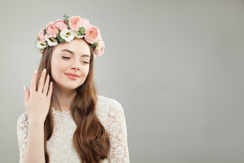 Beleza natural Woman modelo bonito com cabelo encaracolado longo, pele saudável, composição Nude natural e flores fotografia de stock