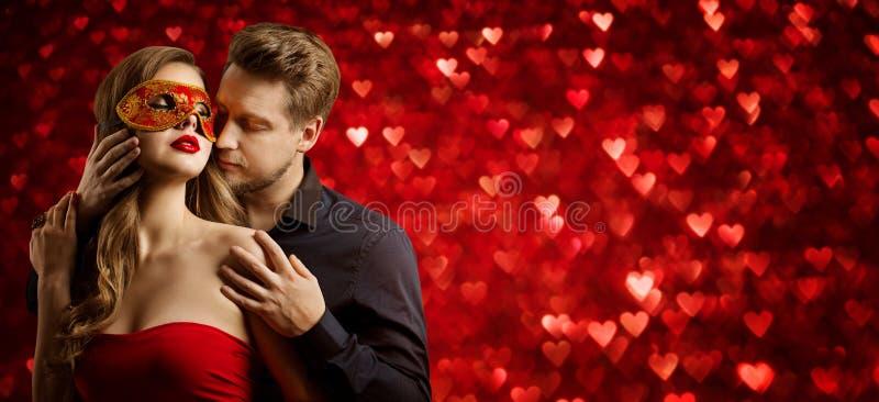 Beleza no Amor, Homem beijando mulher em máscara em corações vermelhos imagens de stock royalty free