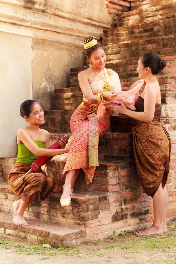 A beleza nobre asiática com as empregadas domésticas vestiu-se na roupa tradicional que compram no tema retro velho do período hi fotografia de stock