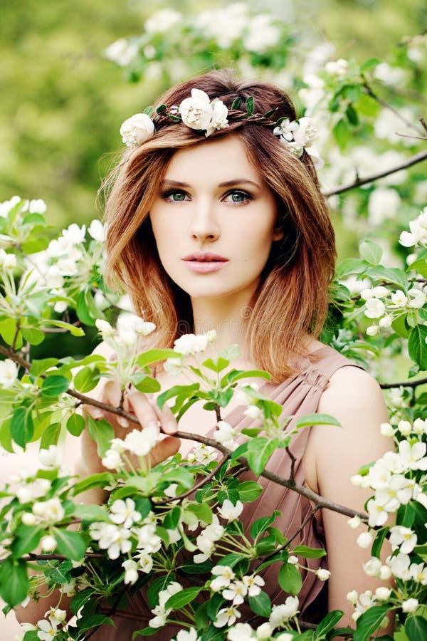 Beleza nova A mulher bonita nas flores envolve exterior foto de stock
