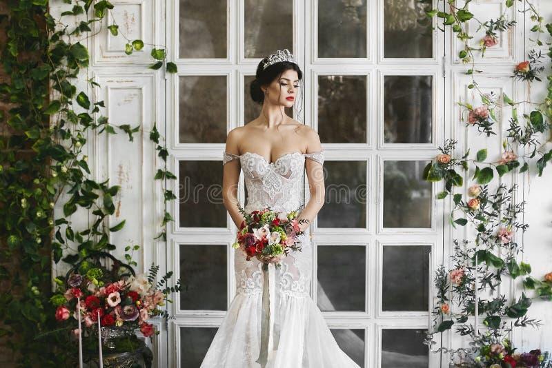 Beleza surpreendente, morena pechugóa, menina modelo com o diadema em sua cabeça e em um vestido do laço do casamento imagens de stock royalty free