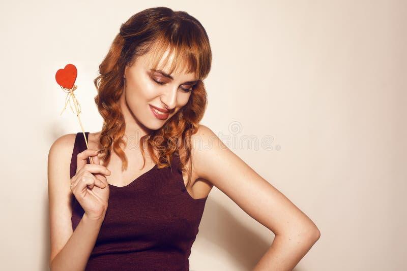 A beleza surpreendeu o modelo de forma novo Girl com Valentine Heart deu forma à cookie à disposição Amor Mulher nova bonita foto de stock