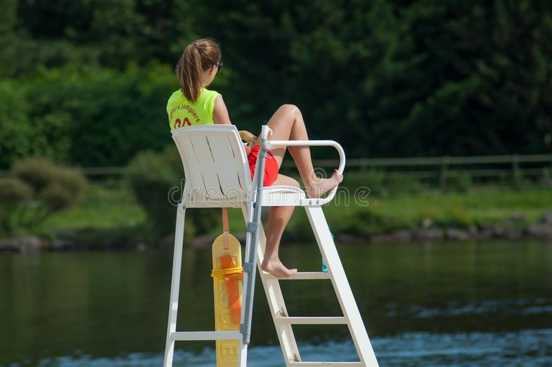 Lifeguard sitting on chair in front of the lake on back view stock images
