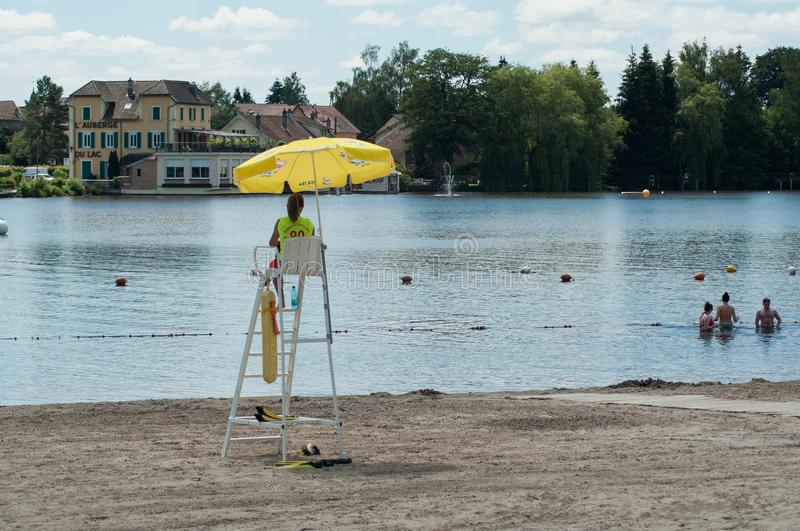 Lifeguard sitting on chair with umbrella in front of the lake on back view stock photo