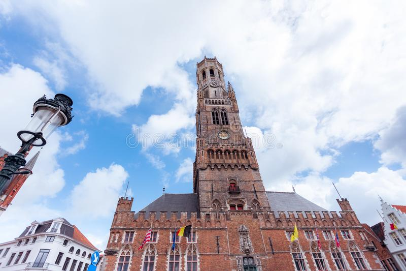 Belfort tower from the square in Bruges, Belgium. Bottom view of the Belfort Tower from the side of the square in Bruges against the background of a beautiful stock images