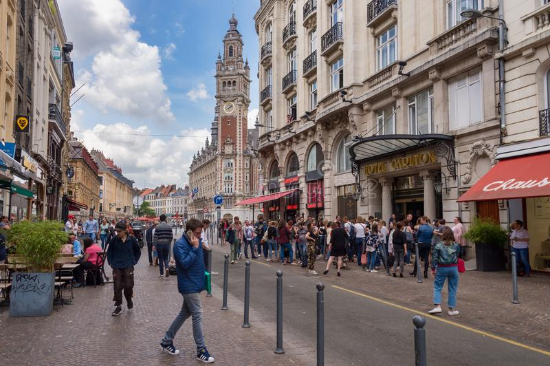 Belfry of the Chambre de Commerce in Lille, FR. Lille, France - 15 June 2018: People walking On Pierre Mauroy street. Belfry of the Chambre de Commerce in the royalty free stock image