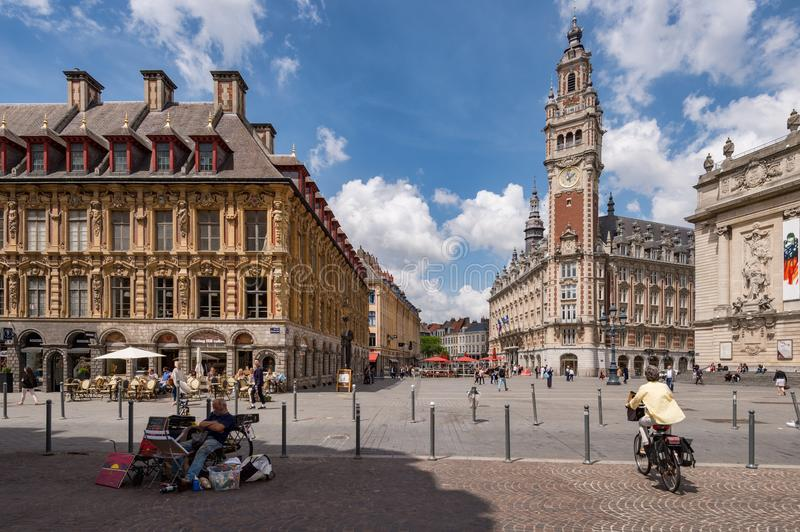 Belfry of the Chambre de Commerce and Opera House in Lille, FR. Lille, France - 15 June 2018: People walking in the Theatre Square. Belfry of the Chambre de royalty free stock photography