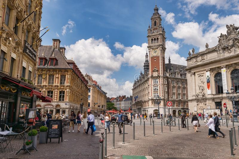Belfry of the Chambre de Commerce and Opera House in Lille, FR. Lille, France - 15 June 2018: People walking in the Theatre Square. Belfry of the Chambre de stock image