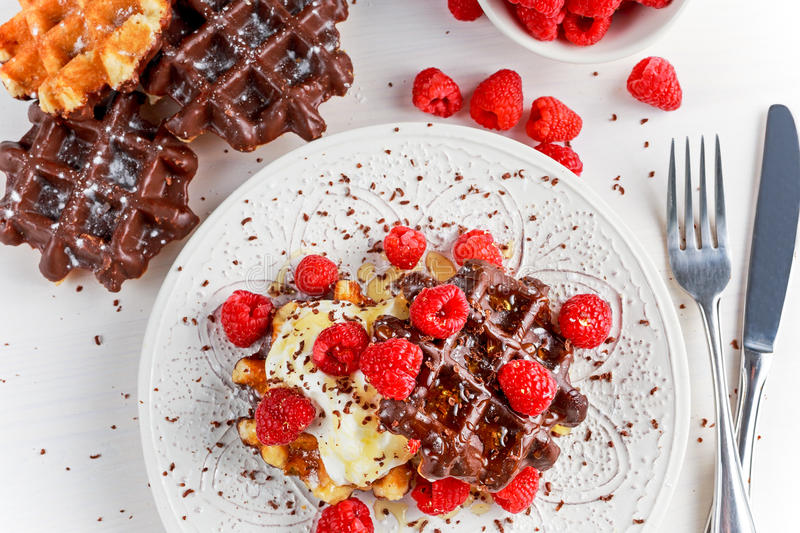 Belgian chocolate waffles with fresh raspberries, whipped cream and honey syrup.  stock photos