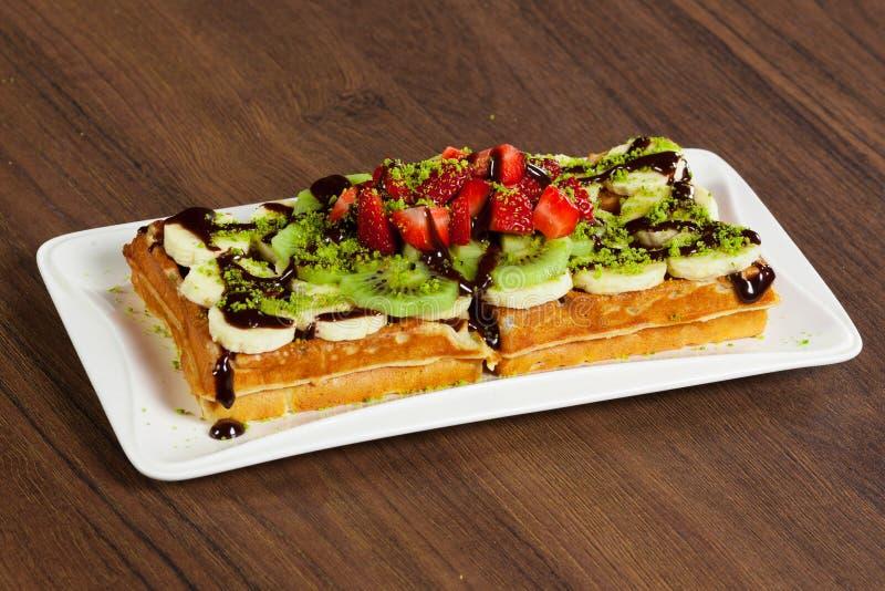 Belgian chocolate waffles with strawberries, kiwi, banana and chocolate royalty free stock image