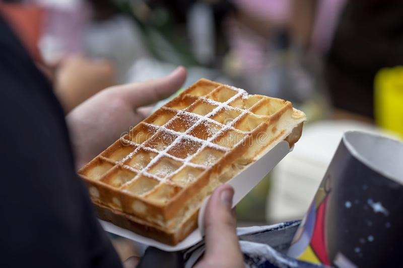 Belgian fresh warm waffle with powdered sugar in hands of buyer. Gastronomic dainty products on market counter, real stock images